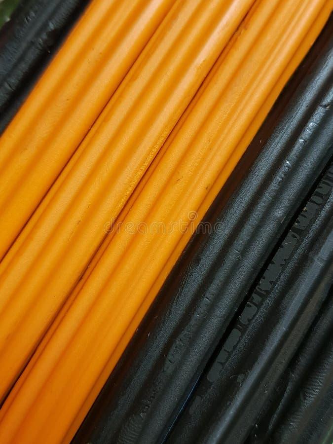 extracto con las barras del plasticine en color, fondo y textura negros y anaranjados imagen de archivo