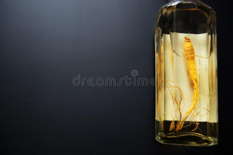 Extracto de raíz del ginseng en la botella de cristal foto de archivo libre de regalías