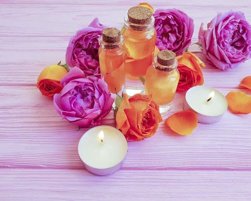 Extracto de Rose, balneario de la vela en fondo de madera imagen de archivo libre de regalías