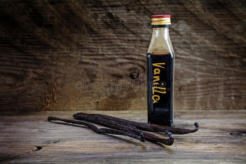 Extracto de vainilla, hecho en casa en una pequeña botella y habas de vainilla encendido imágenes de archivo libres de regalías