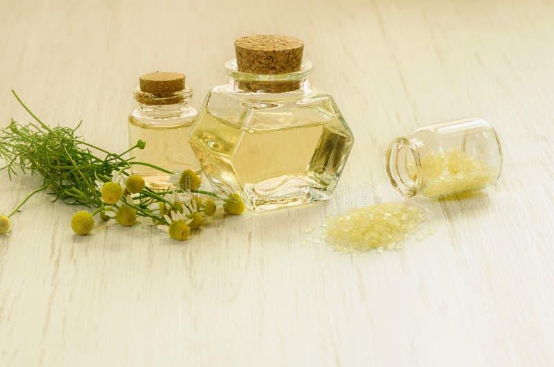 Extracto del agua de la manzanilla de la farmacia en botella, la sal amarilla para el BALNEARIO y las flores frescas como concept imagenes de archivo
