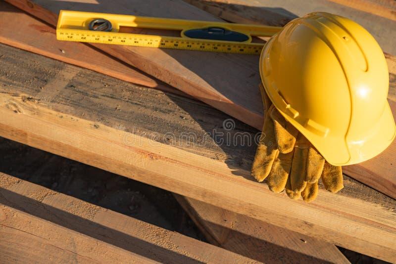 Extracto del casco, de los guantes y del nivel de la construcci?n descansando sobre W imágenes de archivo libres de regalías