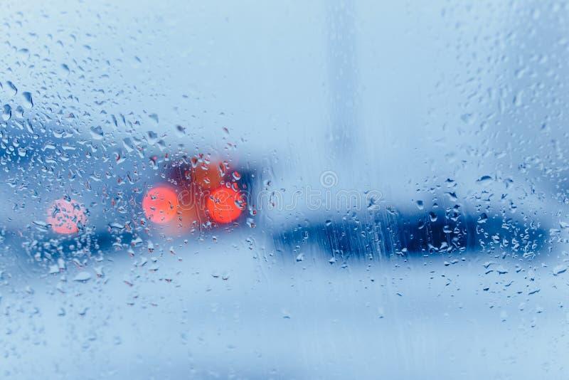 Extracto del tr?fico en lluvia Tr?fico visto por dentro de un coche Gotas de lluvia en luces de la cola del parabrisas y del coch fotos de archivo libres de regalías