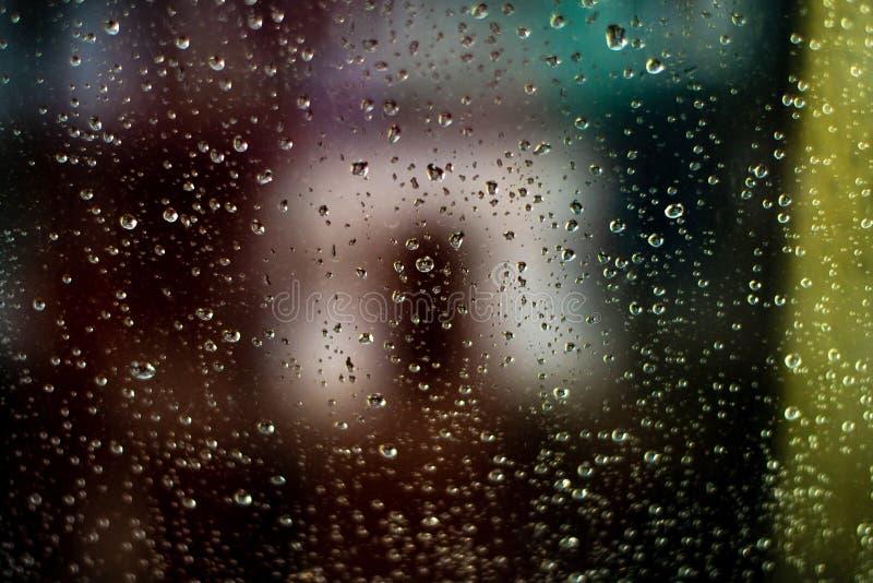 Extracto del vidrio Lluvia de la tarde Fondo borroso coloreado imágenes de archivo libres de regalías