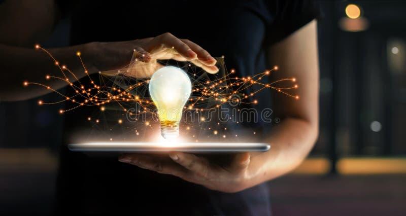 Extracto innovación Manos que sostienen la tableta con futuro de la bombilla foto de archivo libre de regalías