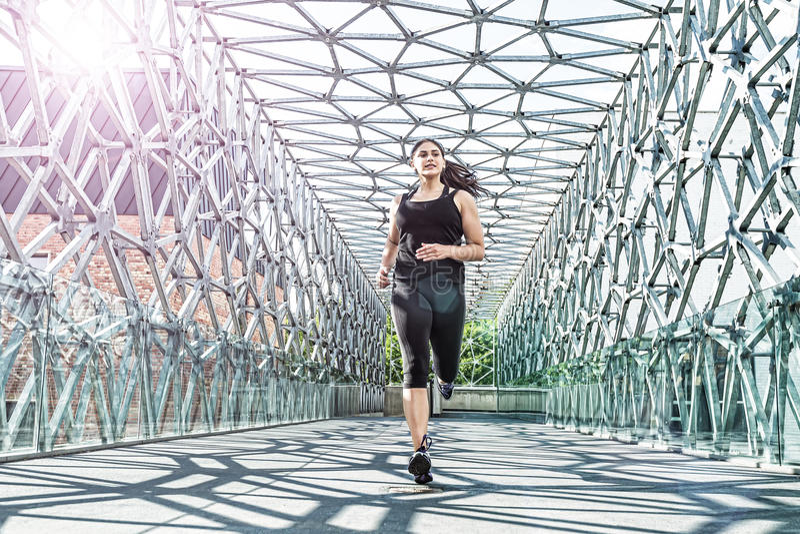 Extracto - mujer hermosa que corre en un puente moderno del metal imagen de archivo