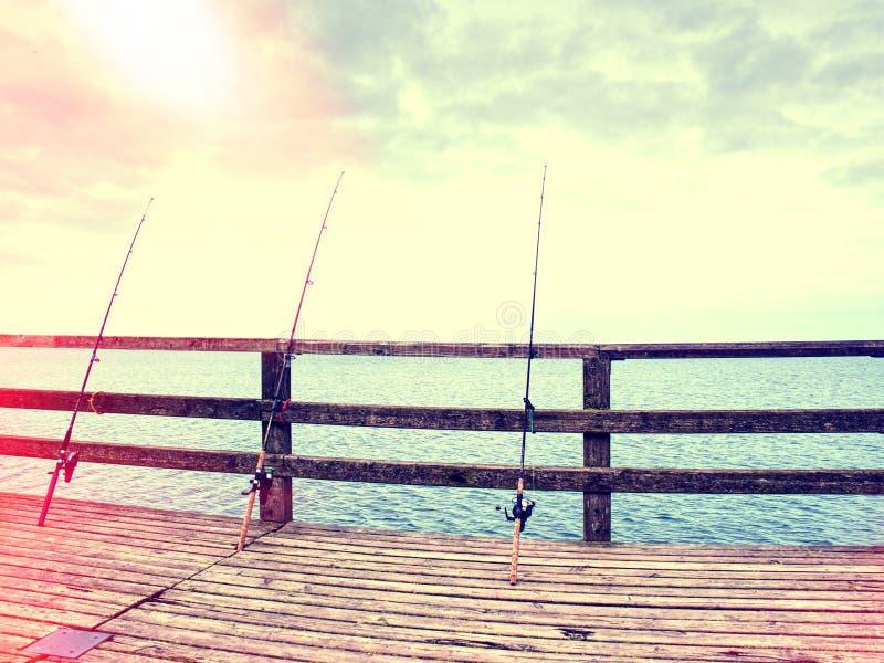 Extracto Varias cañas de pescar contra la verja de madera del embarcadero de la playa foto de archivo