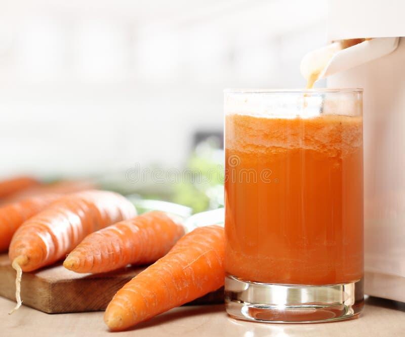 Extractor del jugo y jugo de zanahoria foto de archivo