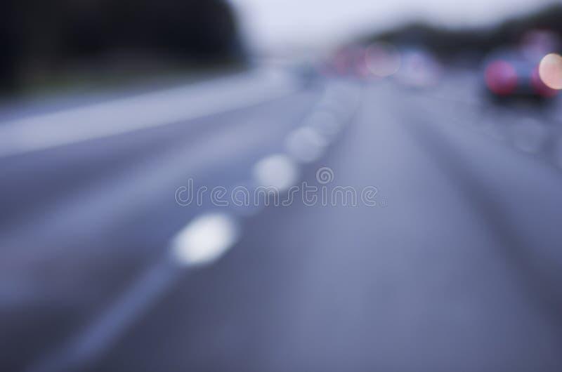 Extrahieren Sie die unscharfe gefährliche Landstraße des Autos, die auf nasses regnerisches fährt und lizenzfreie stockfotos