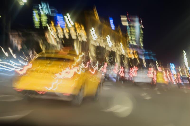 Extrahieren Sie unscharfes Bild des gelben Taxis, städtischen Straßennachtverkehr mit bokeh Lichtern, Nachtzeit, für Hintergrundg stockfotografie
