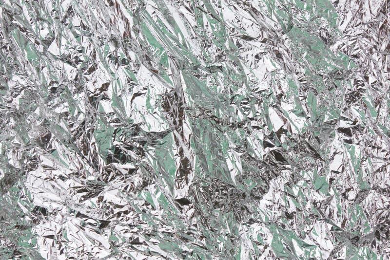 Extrahieren Sie zerknittertes silbernes Aluminiumfolienahaufnahmehintergrund textur lizenzfreies stockfoto