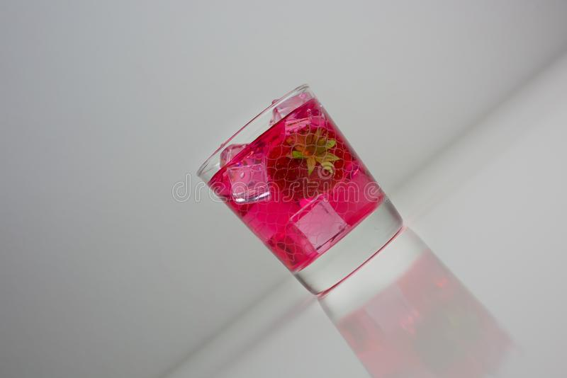 Extrait de jus de fraise versé dans du verre d'eau sur fond blanc images stock