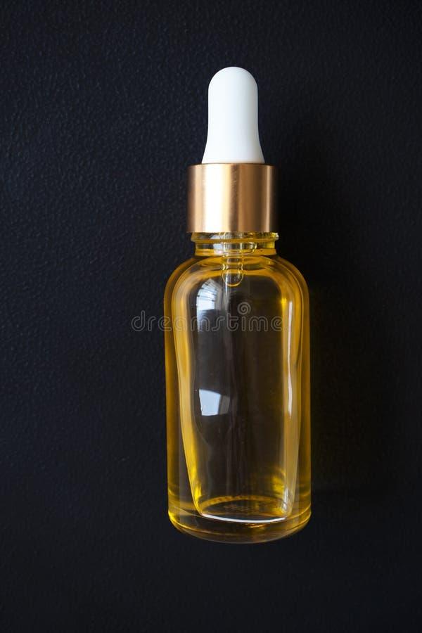 Extrakt för närbildoljaserum i glasflaska på svart arkivfoton
