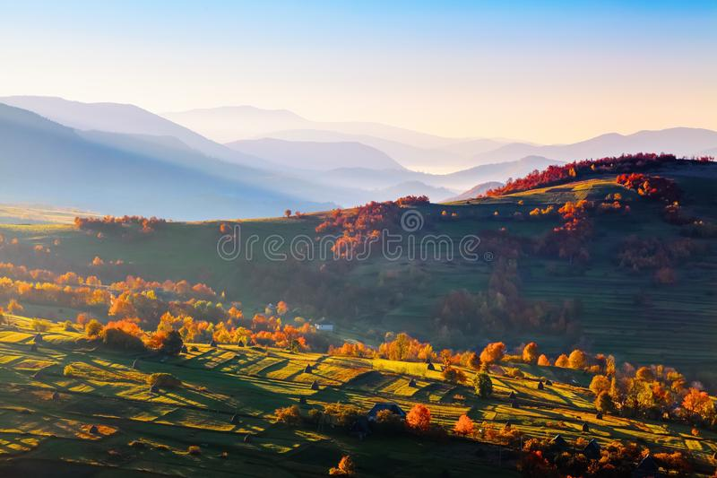 Extraordinary autumn scenery. Green fields with haystacks. Trees covered with orange and crimson leaves. Mountain landscapes. stock images