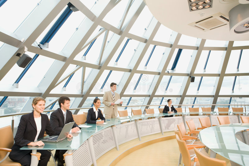 Extraordinary meeting. Businesspeople sitting at the round table listening to their colleague?s speech in large light conference hall with glassy walls