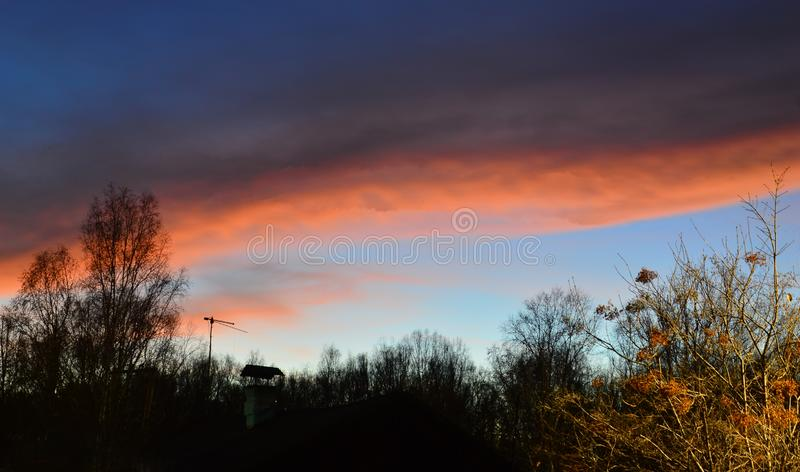 An extraordinary sunset with red clouds. Autumn colors of sunset. An extraordinary sunset with red clouds. Autumn colors at sunset. Silhouettes of the chimney stock photography