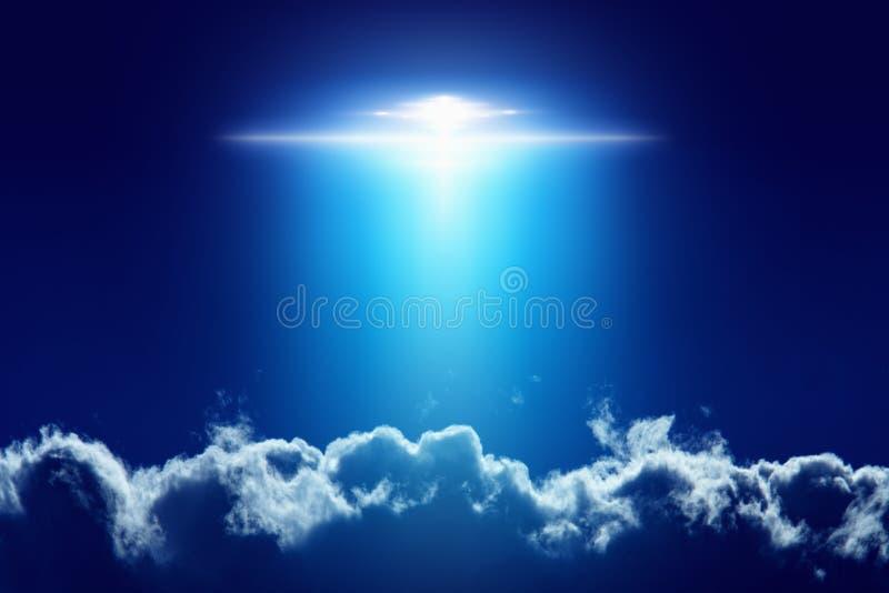 Extraterrestrial aliens spaceship, ufo with bright spotlight in. Fantastic background - extraterrestrial aliens spaceship, ufo with bright spotlight in dark blue stock photo