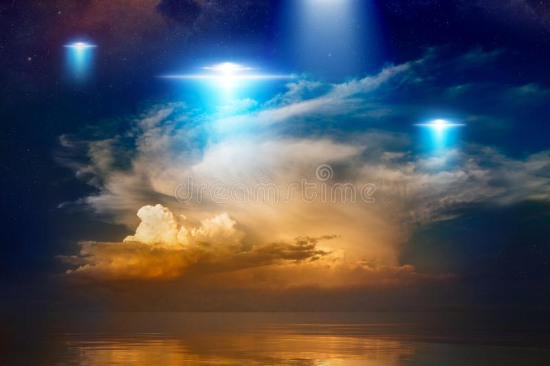 Extraterrestrial aliens spaceships, ufo in red glowing sky. Amazing fantastic background - extraterrestrial aliens spaceship fly above sea, ufo with blue stock photos