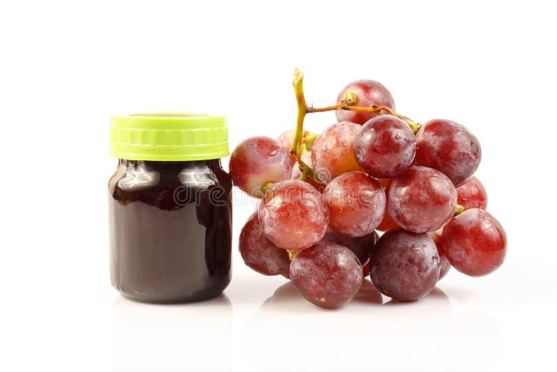 Extrato do suco de uva com a uva fresca no branco imagens de stock
