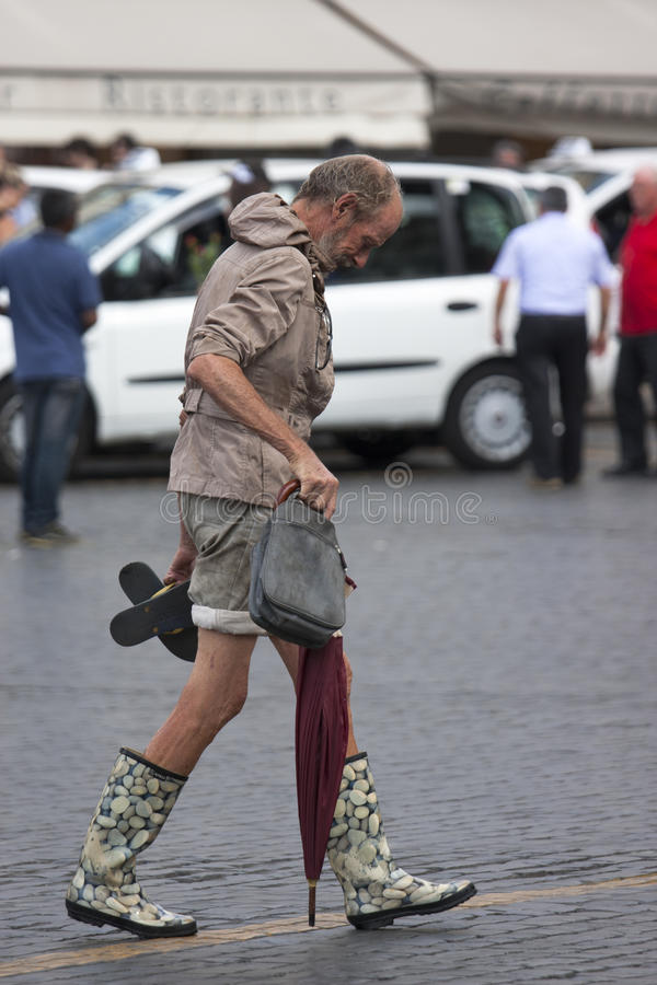 Extravagant clothes man walking. An aged man with extravagant clothing through the center of rome / behind him blurred tourist taxi and restaurant / is wearing royalty free stock images