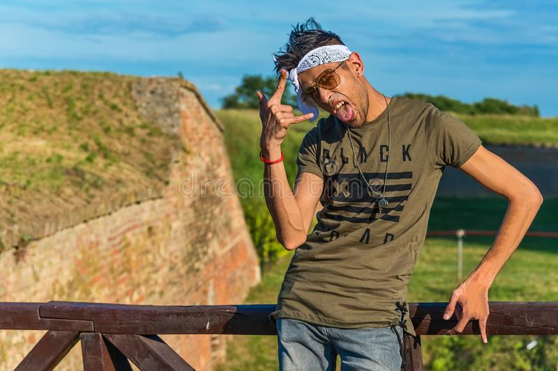 Extravagant hipster male model with sunglasses and a white scarf on a wooden bridge. The model shows the finger as a devilish si. Gn stock photos