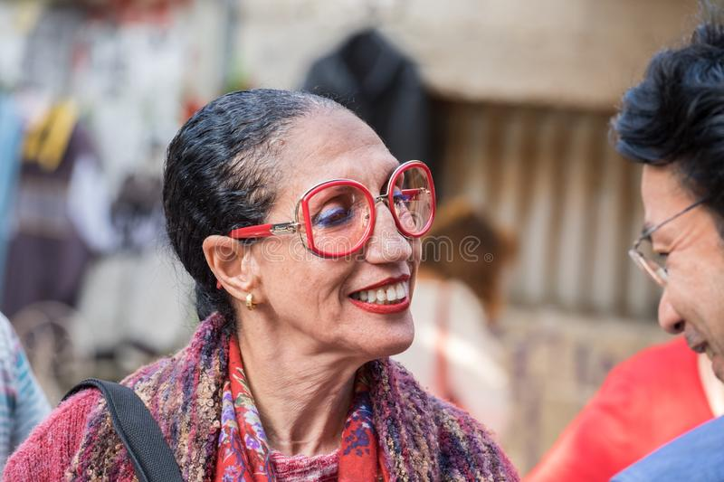 Extravagant middle aged woman at flea market stock photography