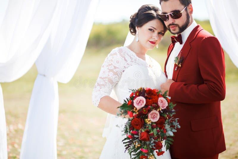 Extravagante bruid en bruidegom, mooi paar, de spruit van de huwelijksfoto Mens in rood kostuum, zonnebril met vlinderdas Zonnige stock foto