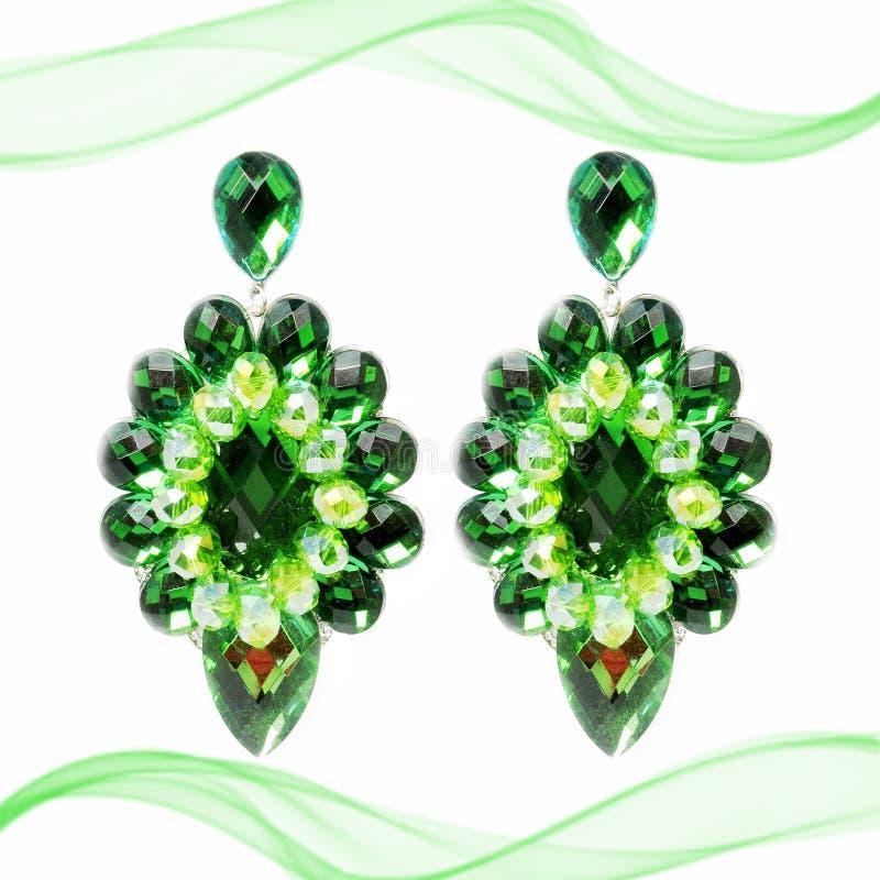 Extravagante große grüne Ohrringe auf einem weißen Hintergrund mit Dekoration lizenzfreie stockfotografie