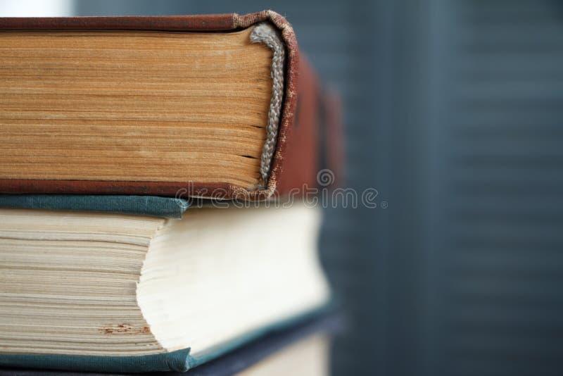 Extreem close-up van een stapel oude boeken, vergeelde pagina's, een gebroken rug van een boek tegen een grijze boekenkast, zacht royalty-vrije stock afbeelding
