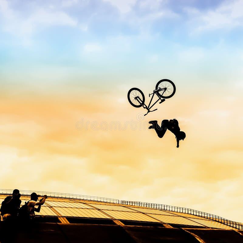 Extrem体育 做与bmx自行车的年轻人剪影跃迁在明亮的天空背景  落的危险的片刻 图库摄影
