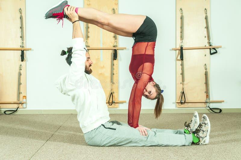 Extrem akrobatisk övning för ung härlig konditionpargenomkörare som förberedelsen för konkurrensen och hagyckeln, selektiv foc royaltyfri bild