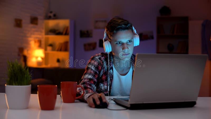 Extrem besorgter Jugendlicher, der Computerspiel auf unbeaufsichtigten Gef?hlen des Laptops spielt lizenzfreie stockbilder