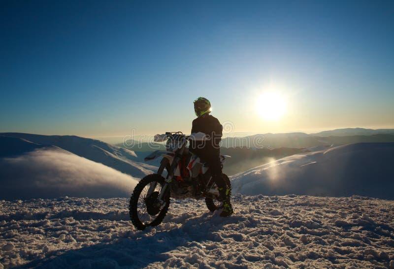 Extrem cyklist på sportmotorcykeln på vintersnöberget på himmel arkivfoto
