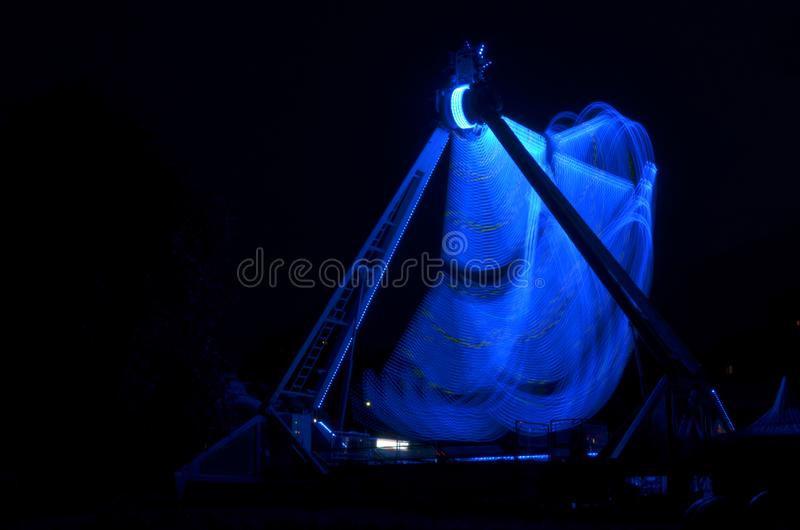 Extrem dragning i Luna Park, med blåa ljus, lång exponeringsskytte i mörker i rörelse royaltyfria bilder