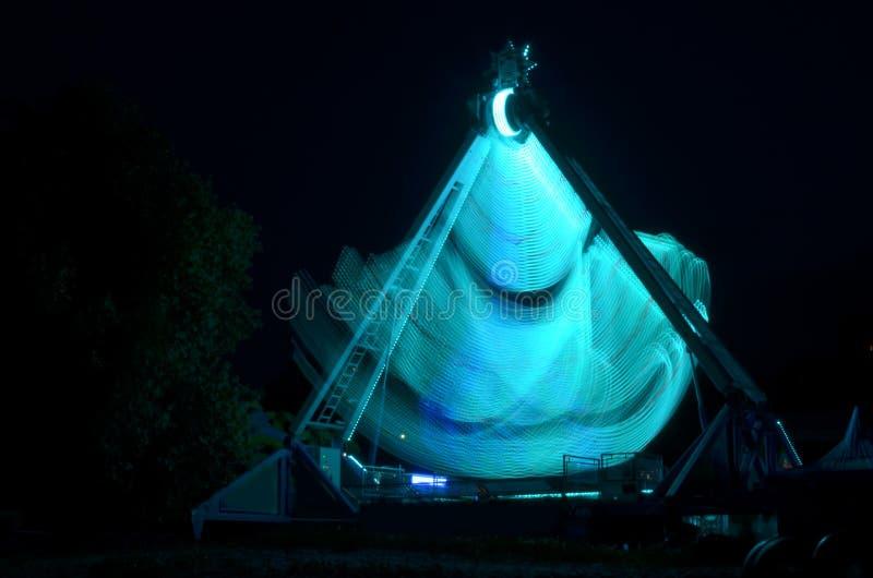 Extrem dragning i Luna Park, med ljust - blåa ljus, lång exponeringsskytte i mörker i rörelse royaltyfri fotografi