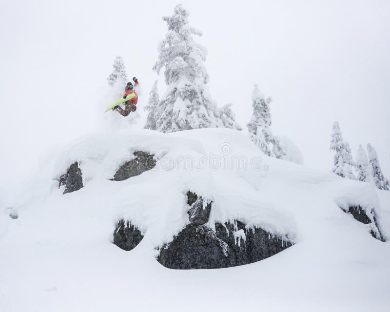 Extrem Snowboarderbanhoppning av pulver Cliff Holding Grab i Backcountry arkivfoto