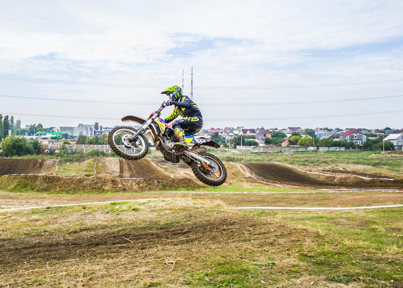 Extrem sportmotocross Idrottsman nen tar av på en motorcykel på en språngbräda Idrottsman nen flyger från sidan på en motorcykel arkivfoto