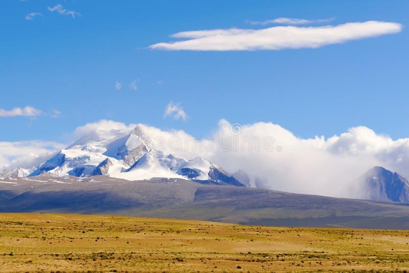 Extrem - tiefe Wolken auf der schneebedeckten Spitze lizenzfreie stockbilder
