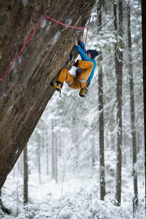 Extrem vintersport Den unga mannen som klättrar en vagga med, belägger Repklättring fotografering för bildbyråer