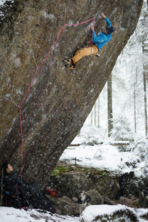 Extrem vintersport Den unga mannen som klättrar en vagga med, belägger Repklättring royaltyfria bilder