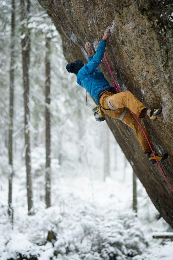 Extrem vintersport Den unga mannen som klättrar en vagga med, belägger Repklättring arkivfoton