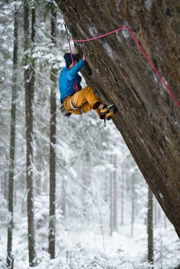 Extrem vintersport Klättring för ung man i härlig Karelian skog royaltyfria foton