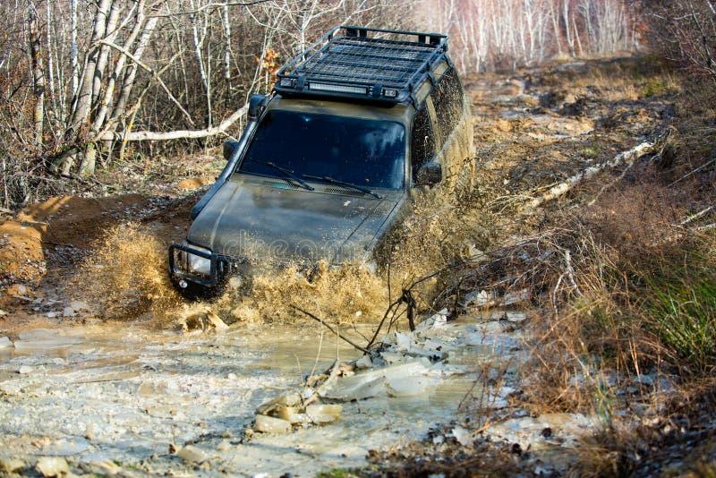 Extrema helger En bil under en tuff av-väg konkurrensdykning i en lerig pöl Konkurrera för chaufför fotografering för bildbyråer