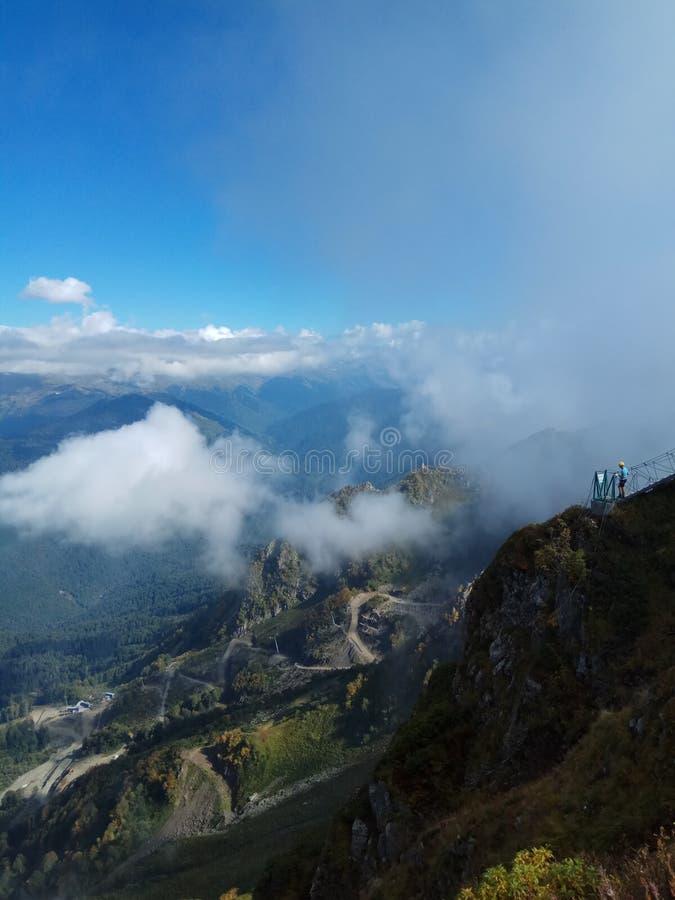extrema turister står på en stenig avsats i bergen f?r russia f?r krasnayabergpolyana f?r sochi f?r snow sky ?verkant sun royaltyfri foto