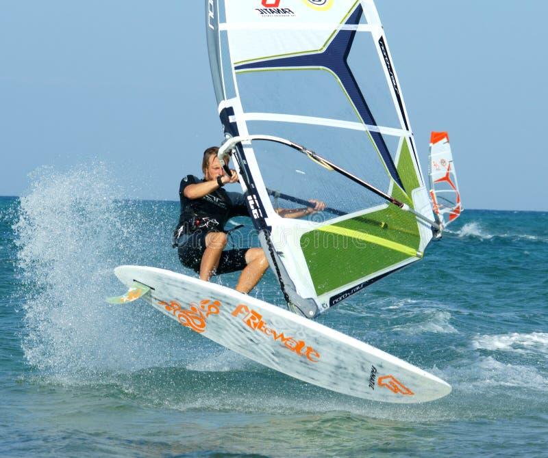 Extremal windsurfing. Extremal windsurfer rides on flat water royalty free stock image