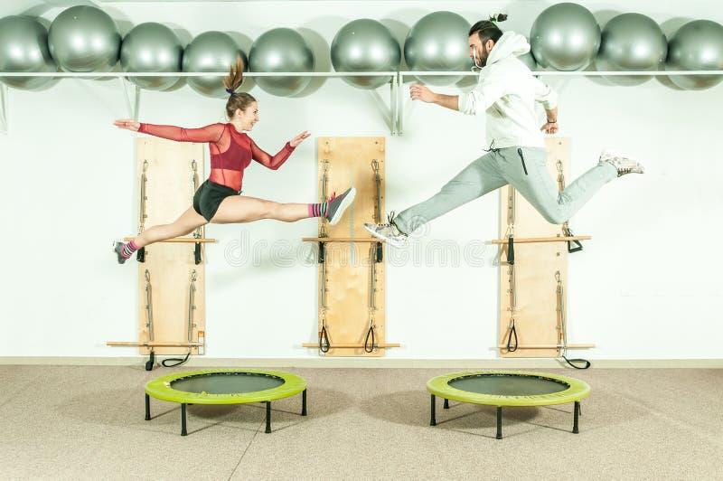 Extreme akrobatische Übung des jungen schönen Eignungspaar-Trainings auf Trampoline springt als Vorbereitung für den Wettbewerb,  lizenzfreies stockbild