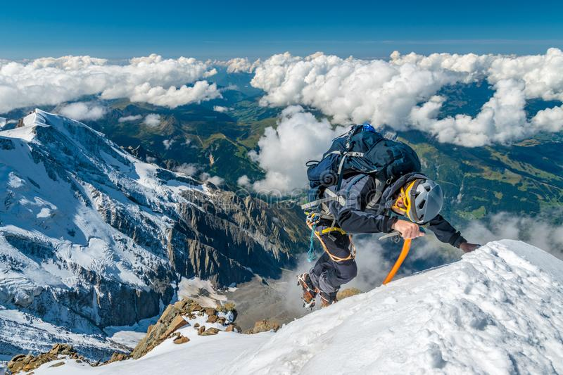 Extreme alpinist in high altitude on Aiguille de Bionnassay mountain summit, Mont Blanc massif, Alps, France. Extreme alpinist in high altitude on a ridge of royalty free stock images