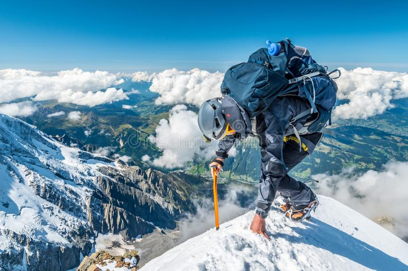 Extreme alpinist in high altitude on Aiguille de Bionnassay mountain summit, Mont Blanc massif, Alps, France, Europe royalty free stock photos