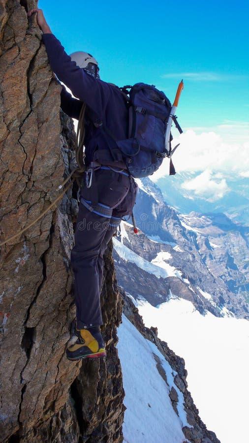 Extreme alpinist op een blootgesteld en verticaal rots en sneeuwgezicht op zijn manier aan een hoge alpiene bergpiek royalty-vrije stock afbeeldingen