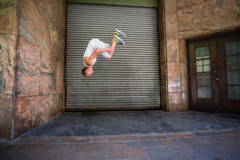 Extreme athlete doing a front flip in front of a building. In the city stock images